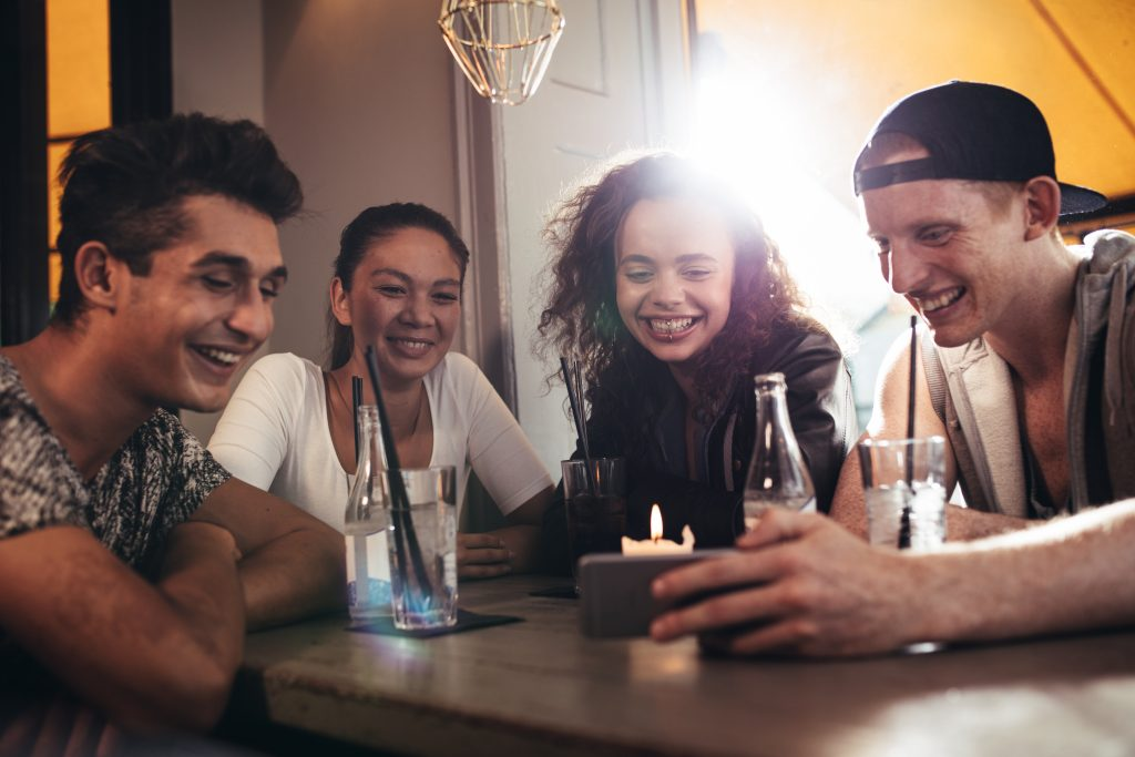 Group of friends sitting together in a cafe looking at mobile phone and smiling. Young guy showing something to his friends on his smart phone.